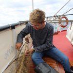 Bootsfrauassistent Thomas beim Knüpfen des Tausendfüßlers