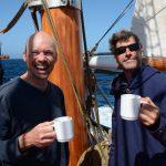 Kapitän und Projektleitung genießen einen Kaffee auf dem Achterdeck